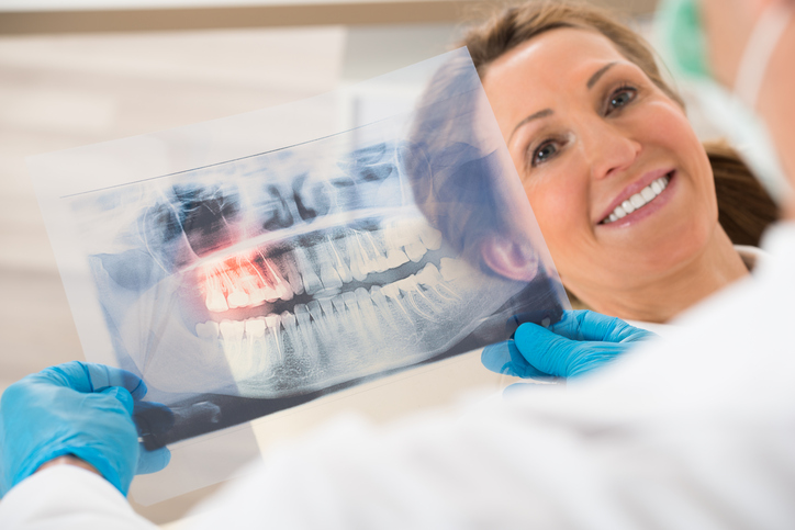 Dentist With Teeth X-ray In Front Of Woman